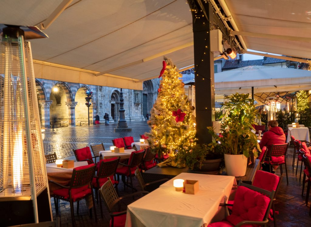 Outdoor dining with heaters under a tent during the winter holidays